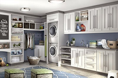 Laundry room has cabinets on two walls designed around stackable washer/dryer system.