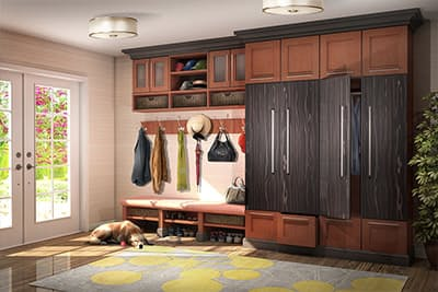 Entry mudroom style bench is custom made withtall hanging cabinets to the right for coats and storage.