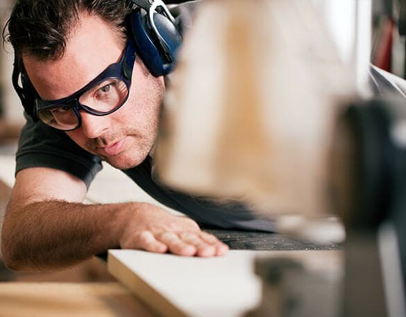 man on sliding table saw in factory making closet pieces for a closet system