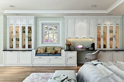 Shaker style wall unit in bedroom has glass cabinets for handbag display.
