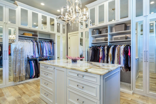 luxury walk in closet in white with an island that has drawers in the center.