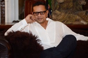 naeem khan sits on a soft at work