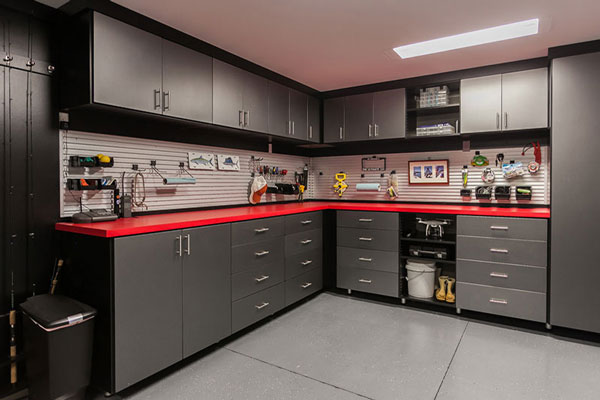 Trendy black garage storage cabinets and red countertop.