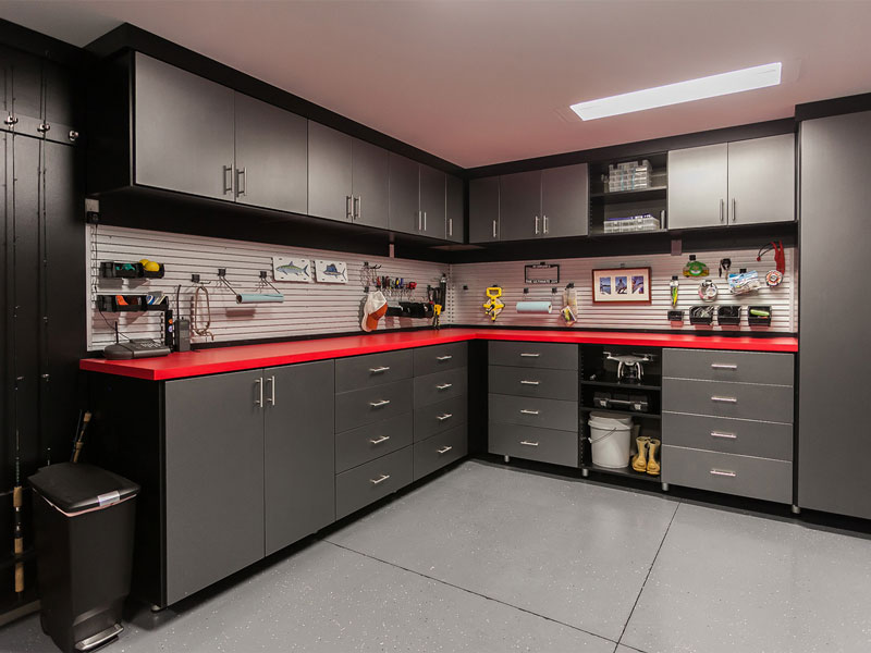Trendy black garage storage cabinets and red countertop make this custom workbench with black uppers a handsome garage system.
