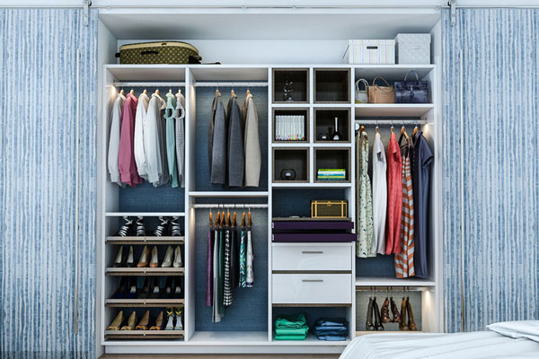 reach-in closet system with slanted shoe shelves, hanging rods, drawers with sweater cubbies, and double hanging