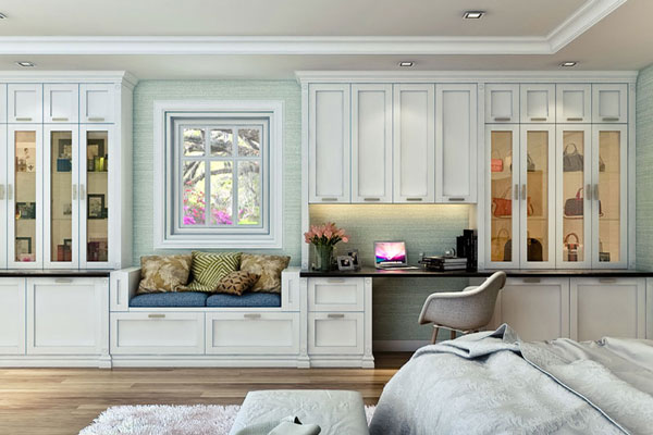 White shaker style custom wall unit in bedroom has window seat and workstation.