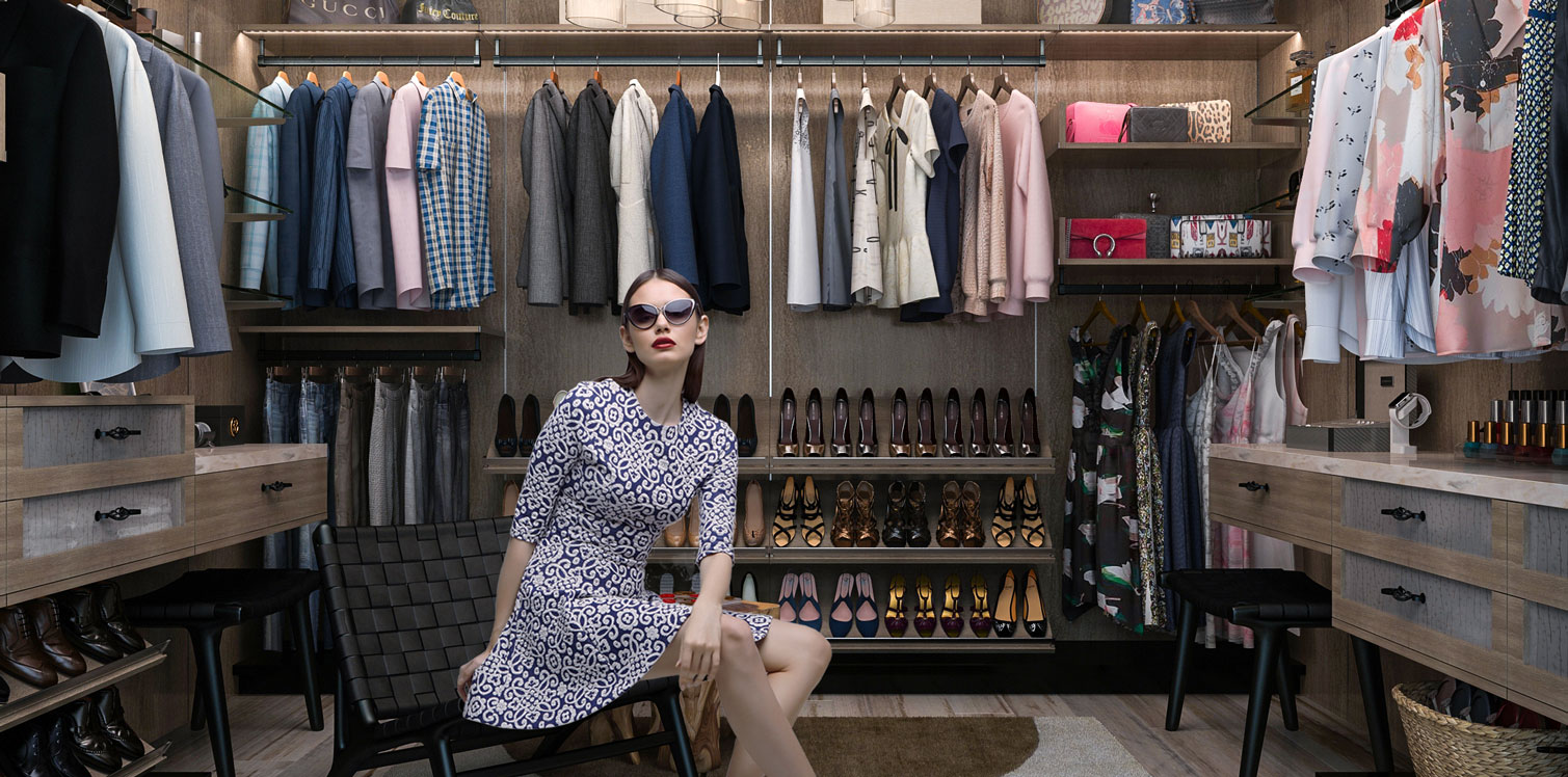 Gorgous trendy woman sits in a walk-in closet system with her wardrobe hanging above slanted shoe shelves and drawers.