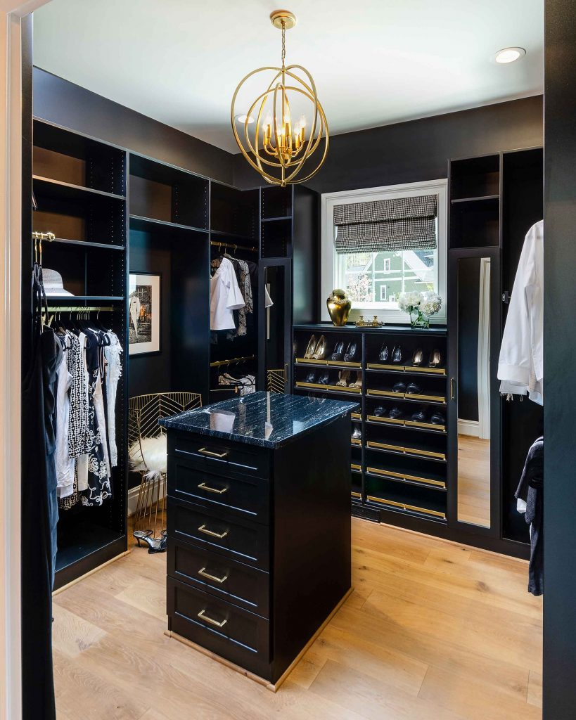 black closet system for walk-in closet with an island.