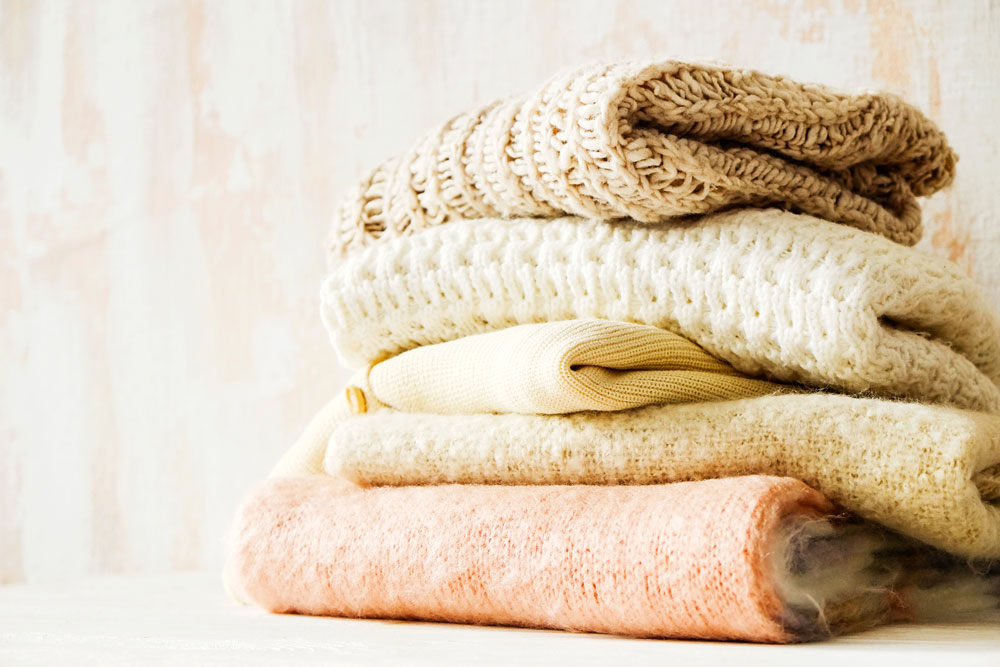pictures of stacked sweaters on a counter