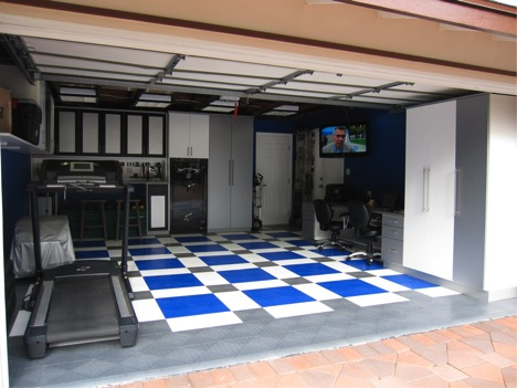 Completed garage with custom cabinetry, flooring, a safe and a built in desk.