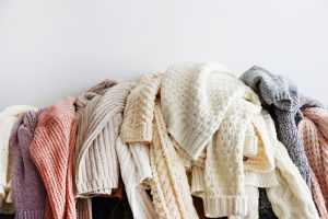 picture of a bunch of sweaters hanging over a couch