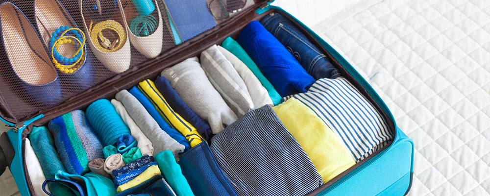 color coordinated wardrobe packed in a suitcase for travel