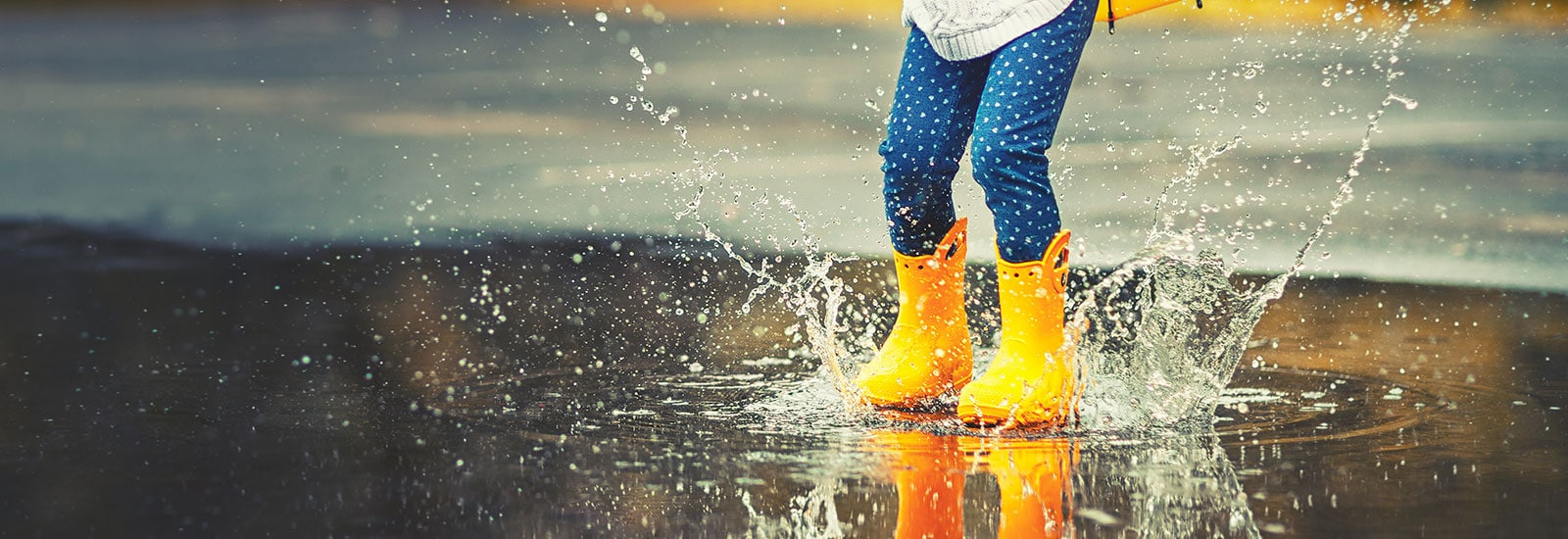 little girl in rain boots in the rain