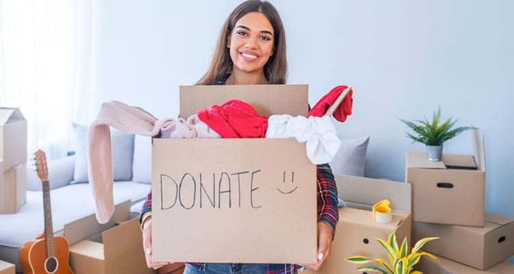 woman holding box of clothing for donation