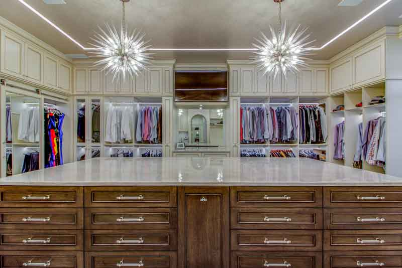 Custom dressing rooms elegantly lighted with chandelier.
