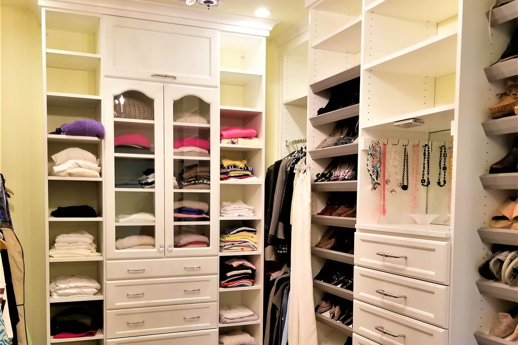 white custom closet with glass inserted cabinet doors