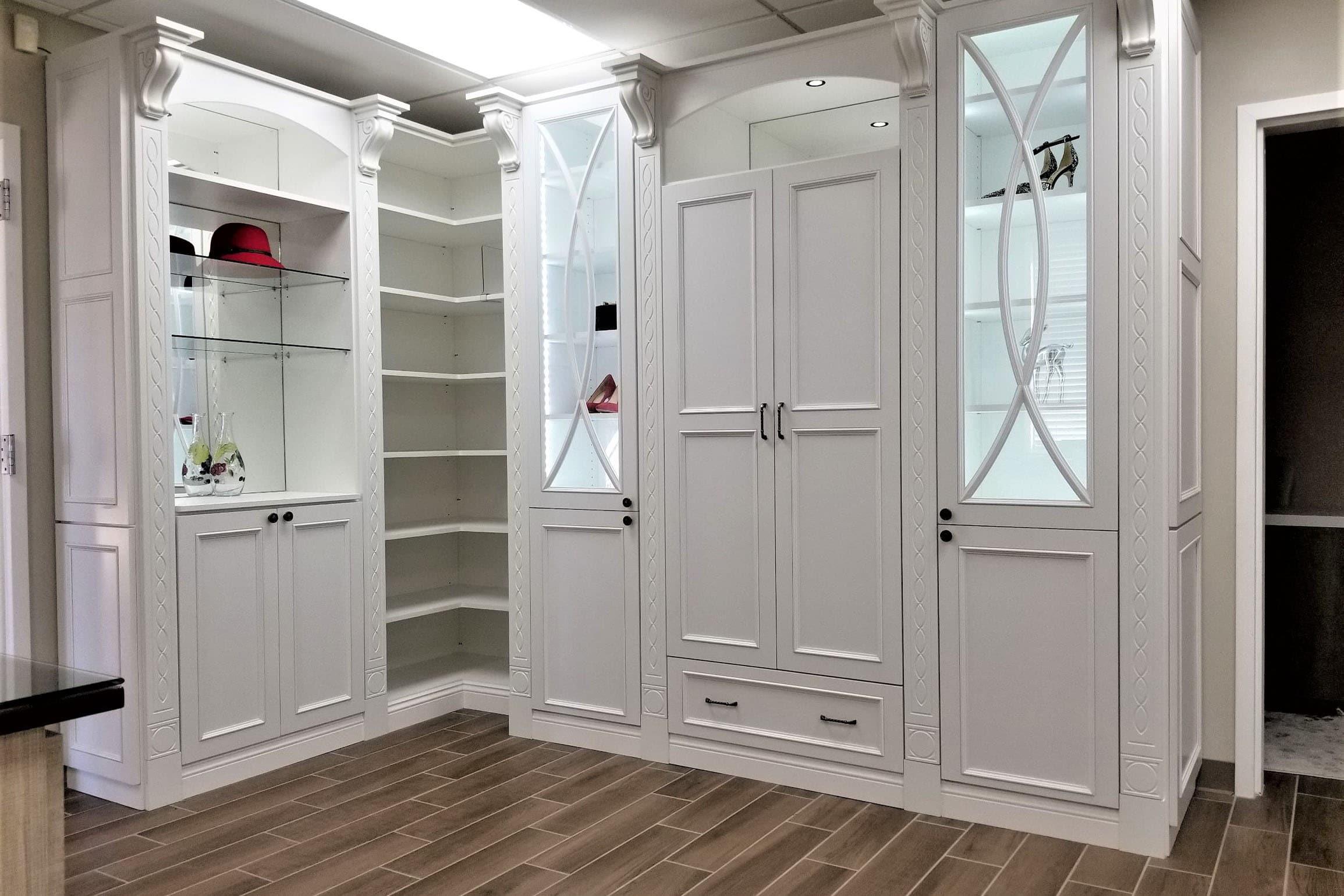 white closet wardobe with glass shelves and luxury molding