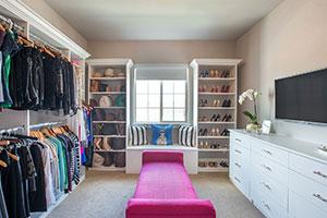 Colorado's White melamine walk-in closet design includes a dresser, shelving framed around window and bright pink bench.