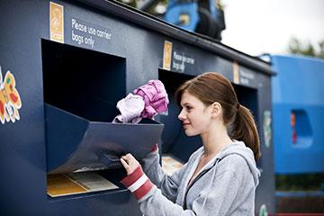 woman donates clothing at drop station