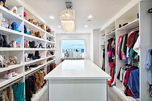 White melamine walk-in closet with boot hanging.