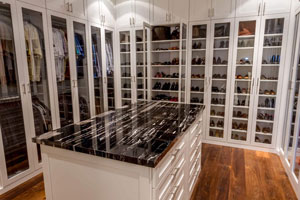 organized walk in closet with glass inserted doors