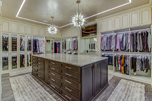 Large walk-in closet features stained walnut island