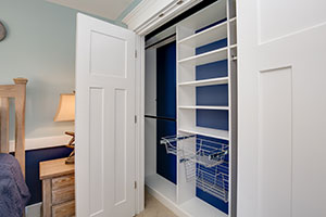 reach-in closet in white melamine with blue wall behind