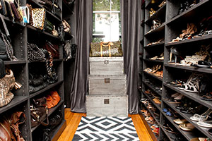 shoe walk-in closet with shoes on left and matching handbags right