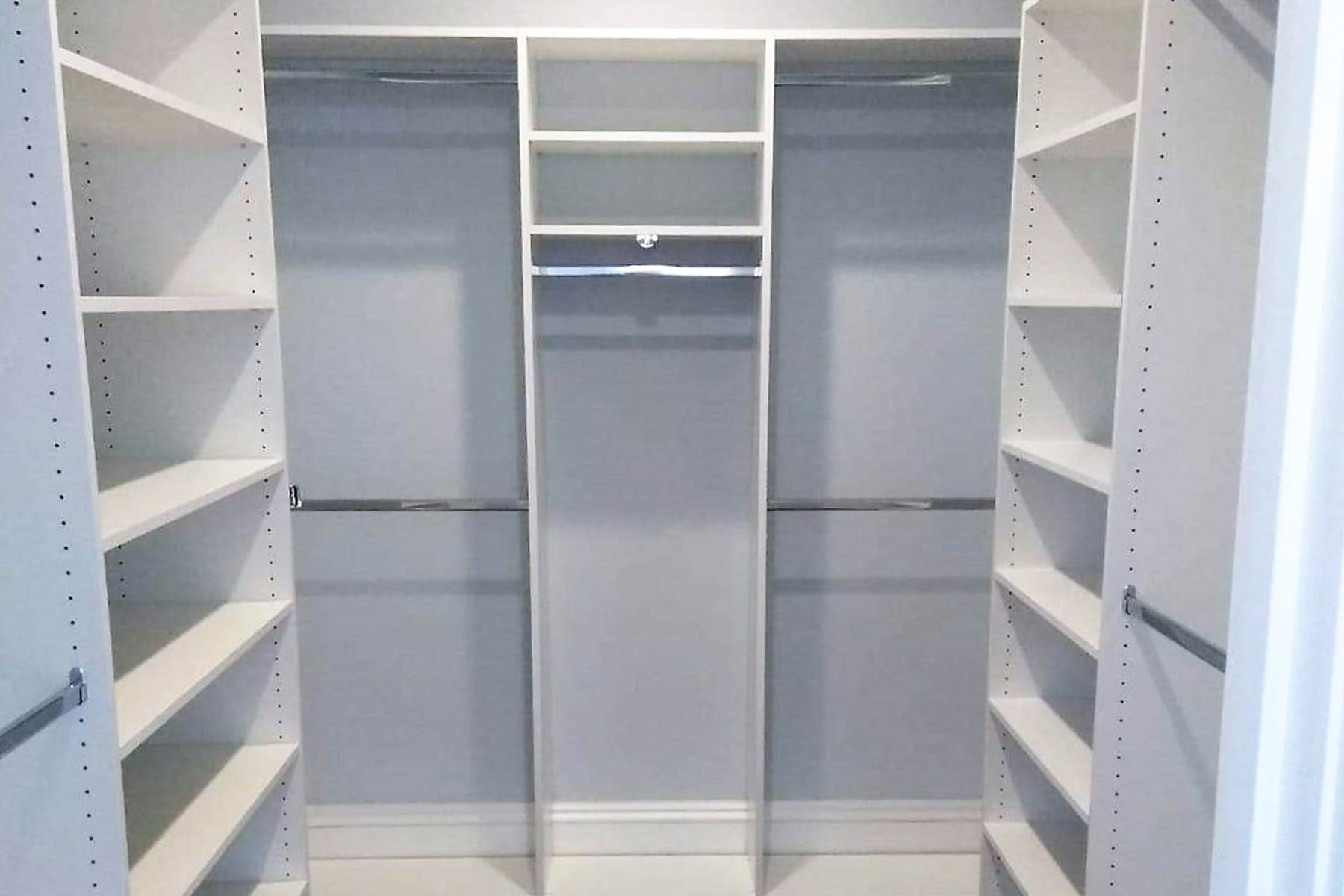 white walk in closet with hanging sections