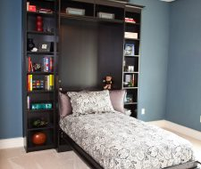 Simple wall bed is built-into black cabinets