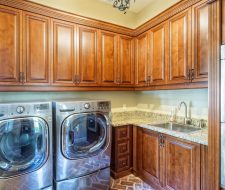 stained custom cherrywood laundry cabinets