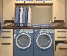 blue washer and dryer laundry room with cabinets