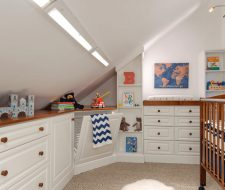 nursery room with built-in cabinets and hamper
