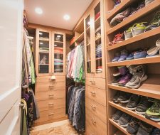 Walkin closet for men with multiple banks of drawers in woodgrain