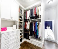 white walk-in closet with shaker style doors and wedding gown display